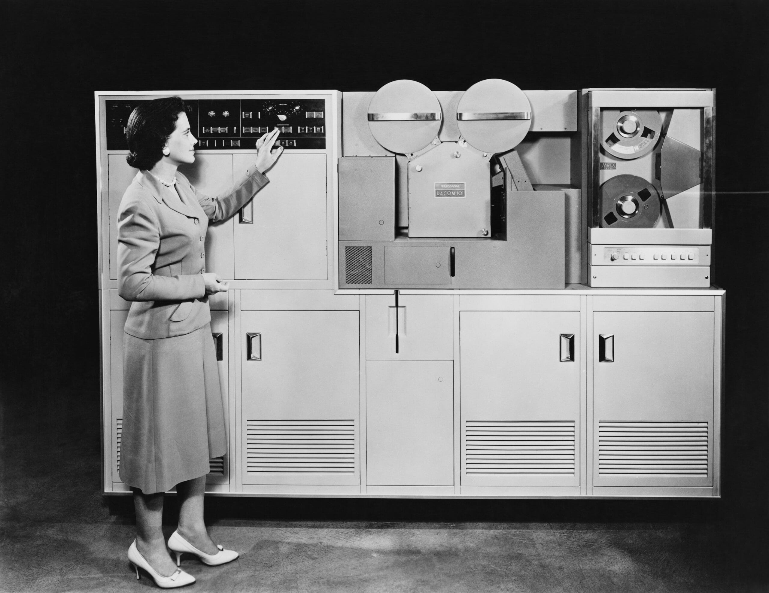 Woman standing in front of a 1950s computer